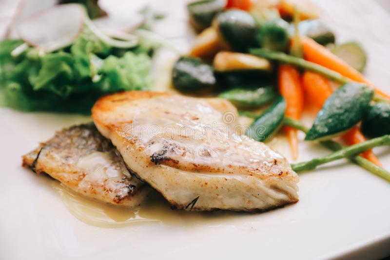 Sea bass fillet with grilled vegetables and salad on wooden tableon a dish stock photography