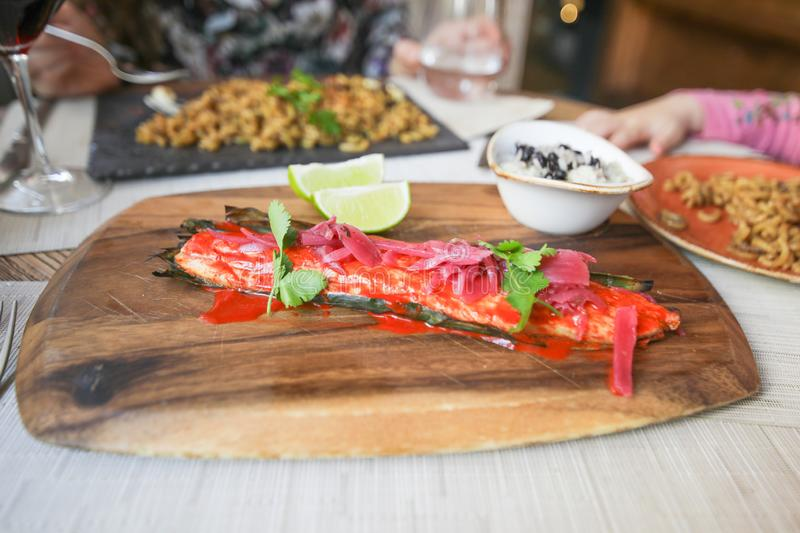 Sea bass fillet with red sauce and marinated onion on wodden tray. Sea bass fillet with red sauce, marinated onion, parsley over plant leaf, with slices of lime royalty free stock photo