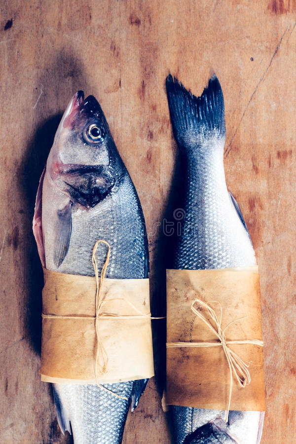 Sea bass fish. Raw on the wooden background stock photos