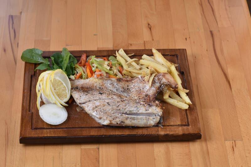 Sea Bass Fish. Served with potato, lemon and salad stock photography