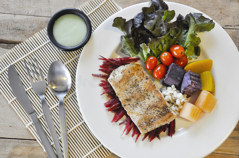 Sea bass Fish steak. On the wooden table royalty free stock photography