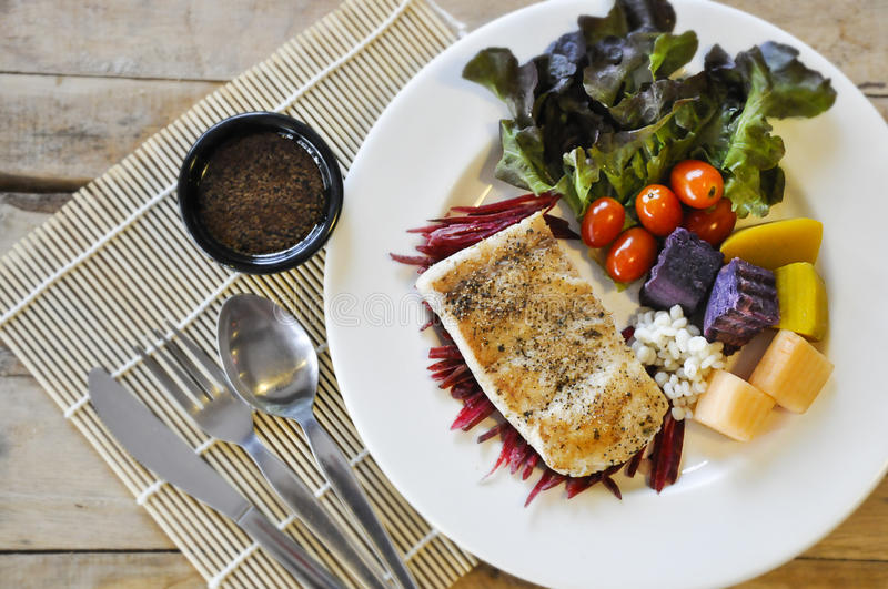 Sea bass Fish steak. On the wooden table royalty free stock image