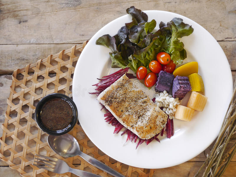 Sea bass Fish steak. On the wooden table royalty free stock images