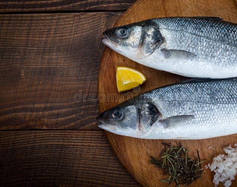 Sea bass fish. Two sea bass fish on cutting board royalty free stock photo