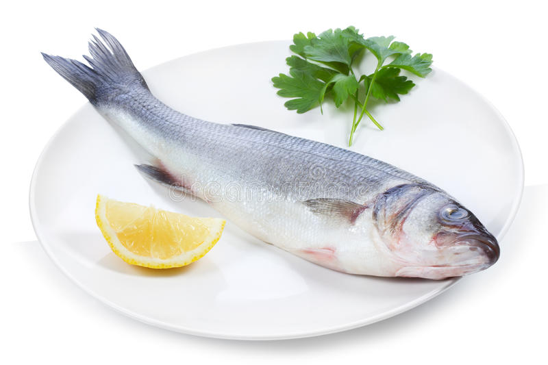 Sea bass with lemon with lemon. And parsley on a plate on white background royalty free stock images
