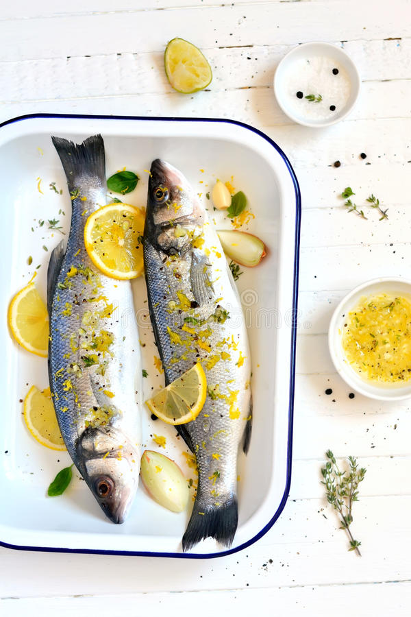 Sea bass with lemon and thyme. On a light background stock photography