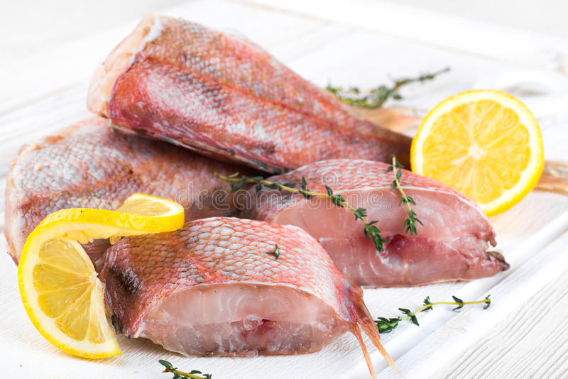 Sea bass. With lemon on wooden board stock image
