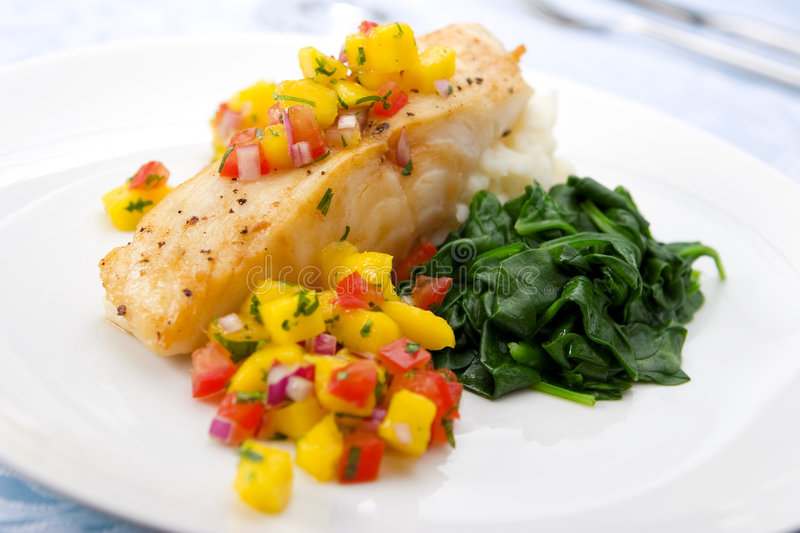 Sea bass with mango salsa. Pan-seared chilean sea bass served with mango salsa, mashed potato and spinach. Shallow DOF royalty free stock photos