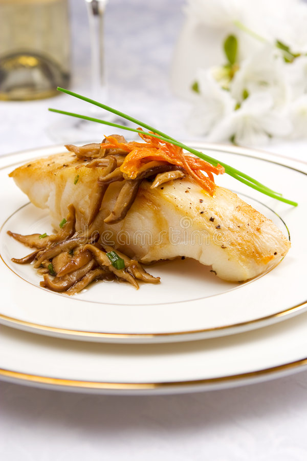 Sea bass with mushrooms. Pan seared Chilean sea bass with shiitake mushrooms royalty free stock photos