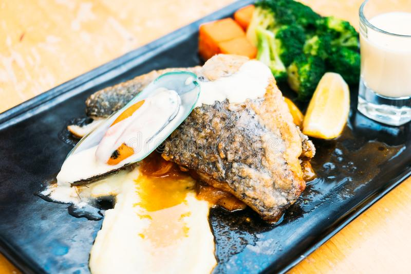 Sea bass and mussel steak. In black plate royalty free stock photo