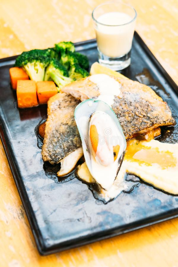 Sea bass and mussel steak. In black plate stock image