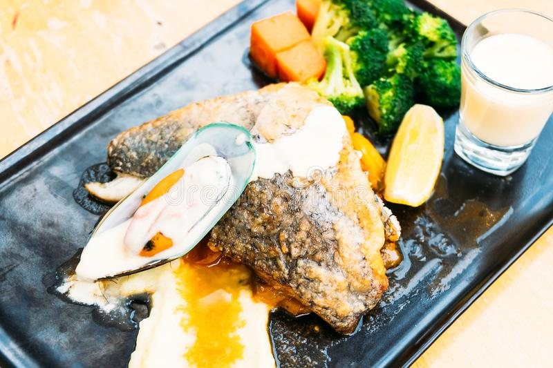Sea bass and mussel steak. In black plate stock photo