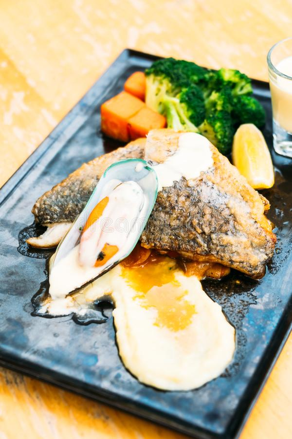 Sea bass and mussel steak. In black plate stock photography