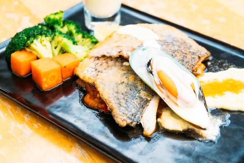 Sea bass and mussel steak. In black plate royalty free stock photos