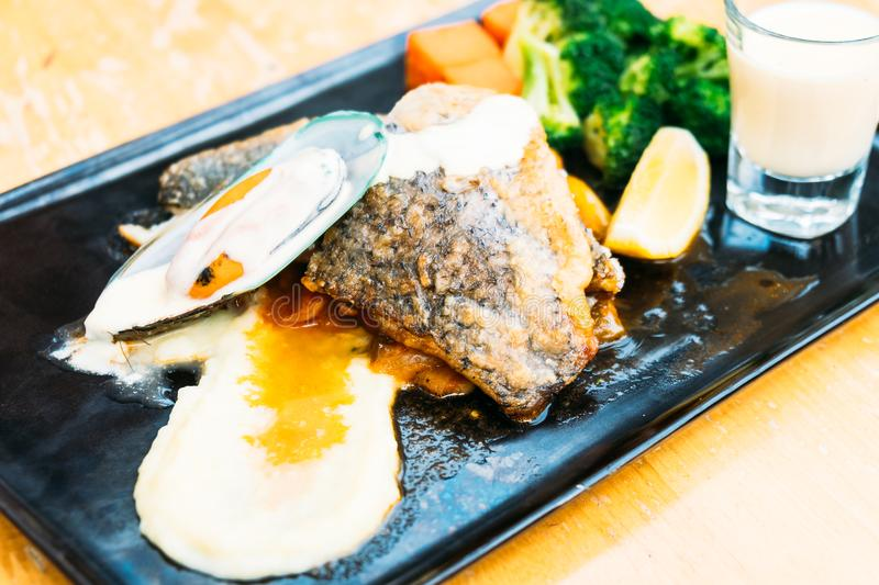 Sea bass and mussel steak. In black plate royalty free stock photography