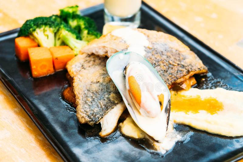 Sea bass and mussel steak. In black plate stock images