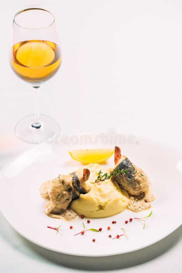 Sea bass in oyster sauce on a white plate on a white background. Sea bass in oyster sauce stock images