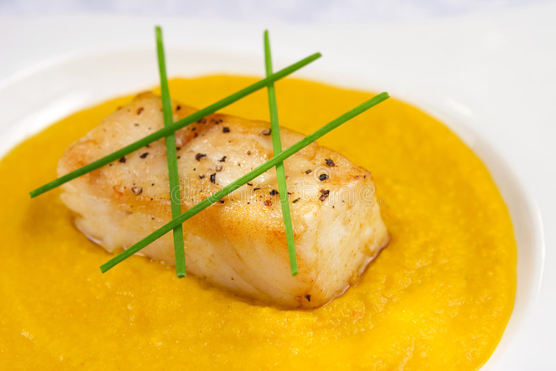 Sea bass with pepper sauce. Pan-seared chilean sea bass on pepper sauce garnished with chives stock image