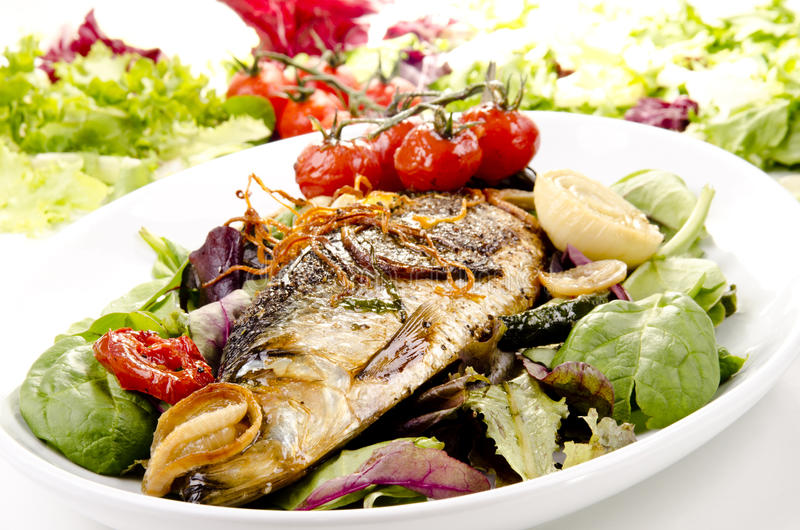 Sea bass on a plate. Grilled sea bass on a plate with fresh salad stock images