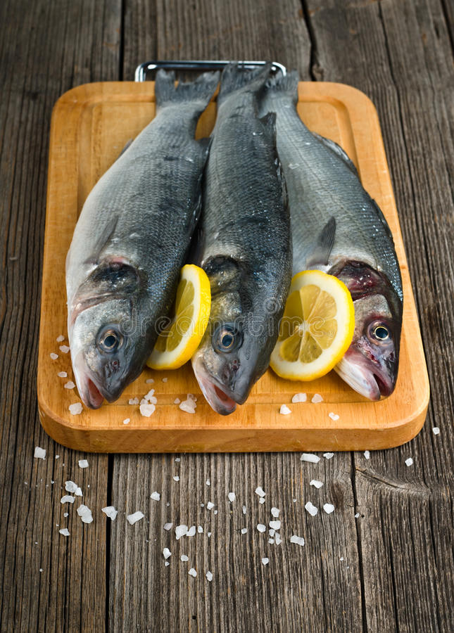 Sea Bass with salt. And lemon on wood background royalty free stock image