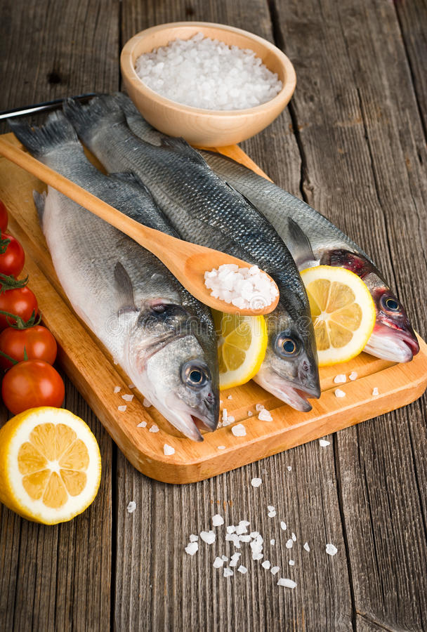 Sea Bass with salt. And vegetables on wood background stock image