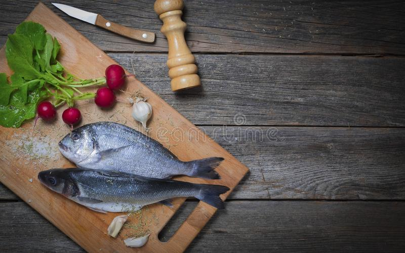 Sea bass and sea bream with vegetables. Fresh European sea bass and Gilt-head sea bream with vegetables and garlic on a wooden background royalty free stock images