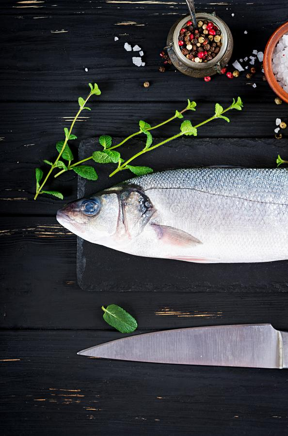Sea bass on slate blackboard. Ingredients for cooking, grill, baked. stock photos
