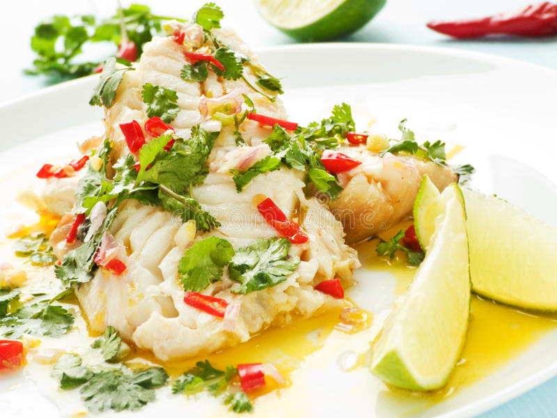 Sea Bass. Steamed sea bass fillet with chili pepper and cilantro in olive and linseed oil. Shallow dof royalty free stock image