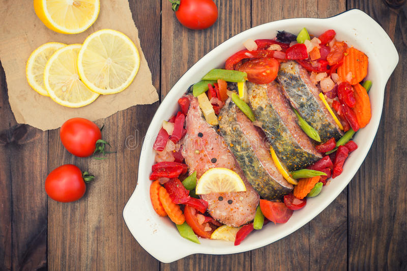 Sea bass with vegetables. marinated fish with vegetables for cooking in the oven. Wooden background. Top view. Close-up. Sea bass with vegetables. marinated fish stock images