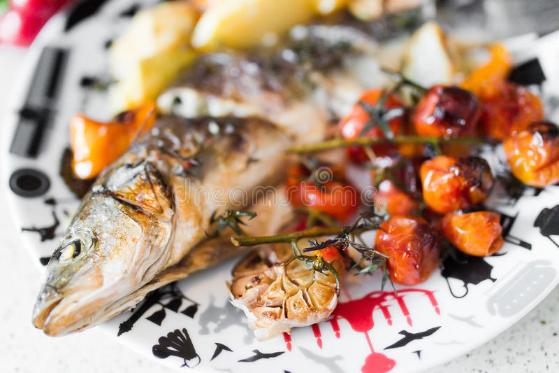 Sea bass with vegetables. On table royalty free stock photo