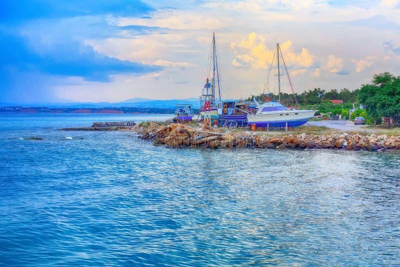 Port of Nea Potidea, Chalkidiki, Greece. Sea bay and old port with boats in Nea Potidea or Nea Poteidea in peninsula Kassandra, Chalkidiki, Greece royalty free stock images