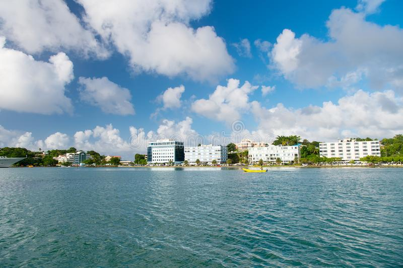 Sea beach with buildings on cloudy blue sky in castries, st.lucia. Summer vacation on tropical island. Travelling, trip and wander stock photo