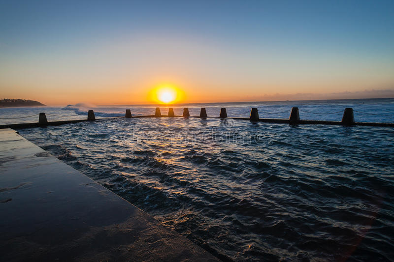 Sea Beach Tidal Pool Waves Sunrise. Ocean waves surging and crashing on high tides with swells breaking large powerful volumes of sea water into the beach royalty free stock image