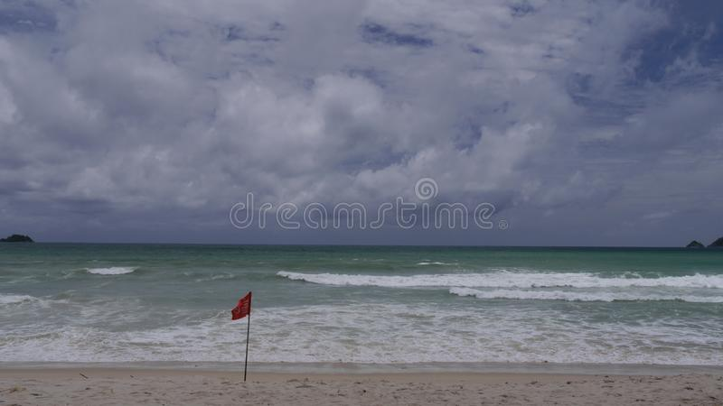 Sea, beach, waves,red flag and blue sky with clouds . royalty free stock images