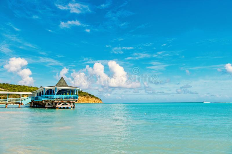 Sea beach with wooden shelter on sunny day in antigua. Pier in turquoise water on blue sky background. Summer vacation stock photos