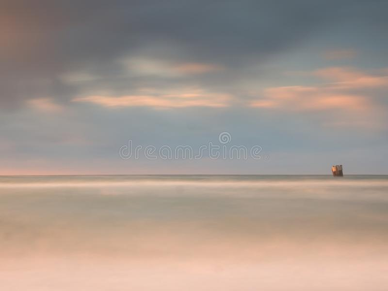 Sea birds on boulder sticking out from smooth wavy sea. Evening wavy ocean. Dark horizon with the last sun rays. Soft focus. Sea birds sit on boulder sticking royalty free stock photo