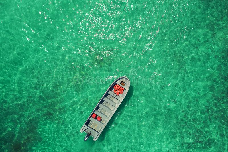Sea boat anchoring next to reef. Aerial top view of motor boat in the turquoise water of caribbean sea. Punta Cana coast royalty free stock photos