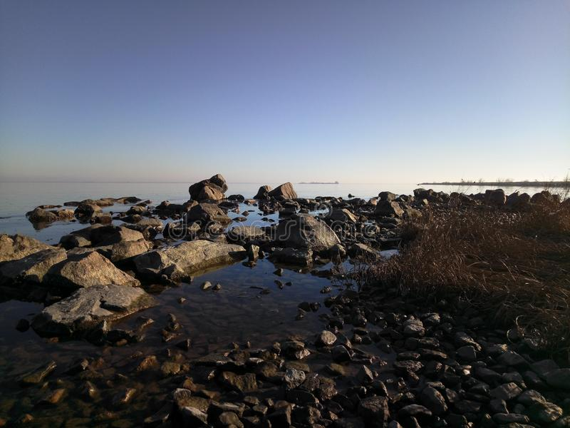 Sea boulders going into the water surface royalty free stock photography