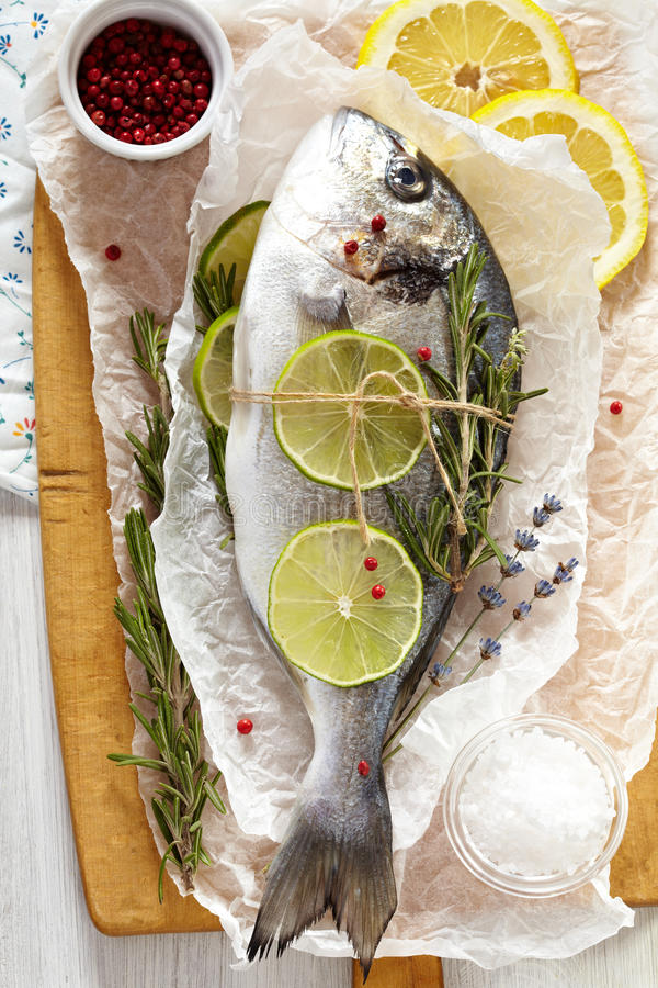Sea bream. Fresh sea bream with lemon, lime, rosemary, salt and pink pepper on wooden cutting board and paper wrapping royalty free stock photography