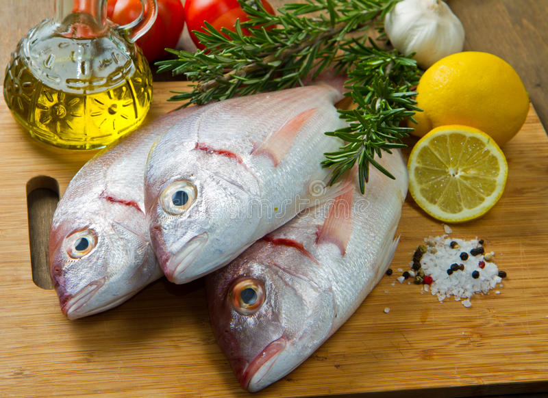Sea bream. A group of sea bream with lemon and rosemary on wood table stock image