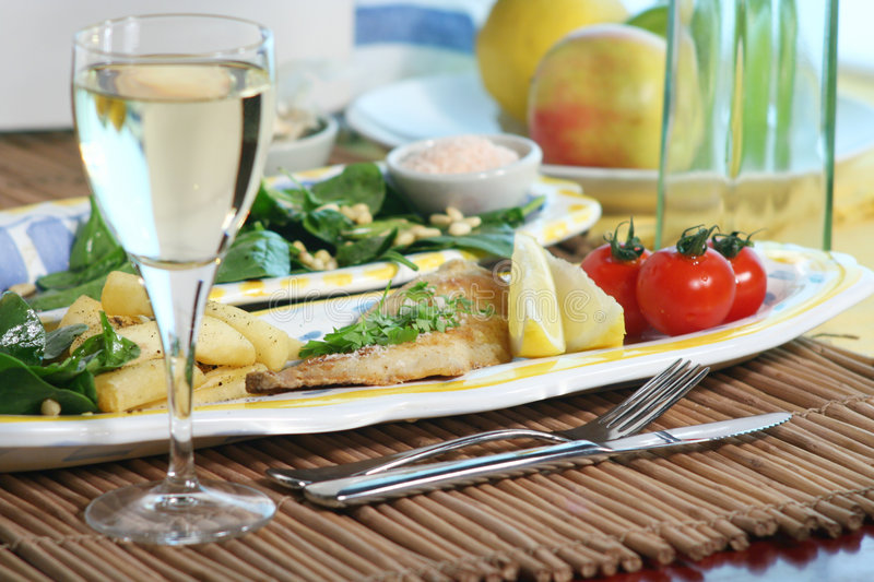Sea bream dinner. Grilled Sea Bream, chips, cherry tomatoes and baby spinach salad with pine nuts. Wine glass in front royalty free stock photos