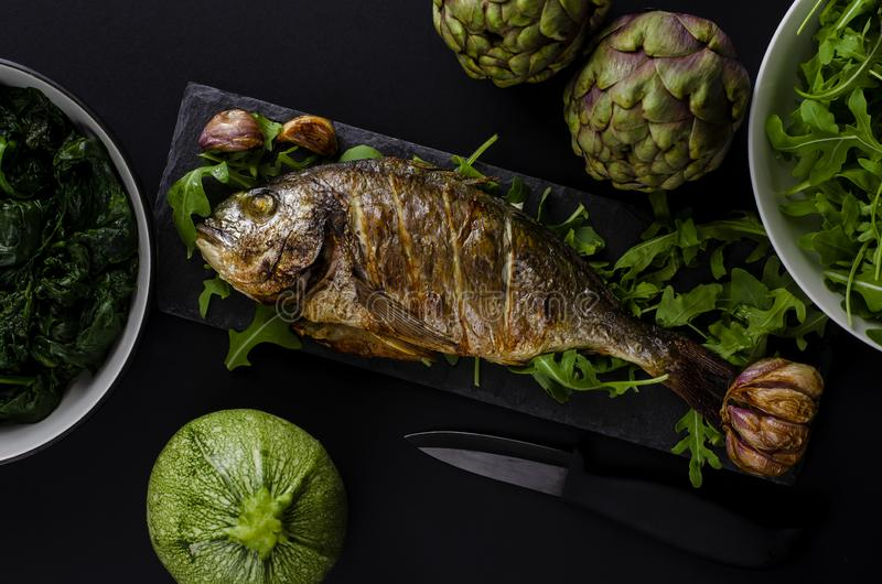 Sea bream or dorada fish baked in oven on black royalty free stock image