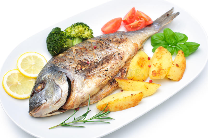 Sea bream fish. With potato on white plate stock images