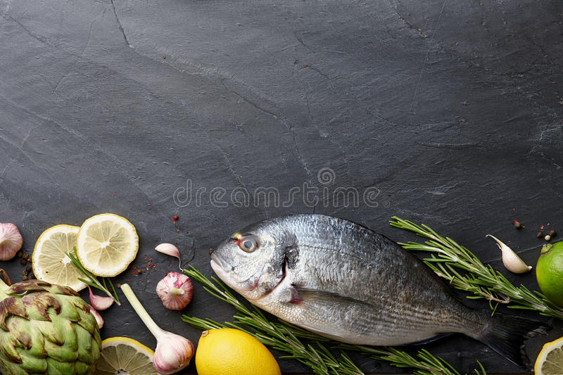 Sea bream fish cooking. Fresh raw sea bream fish cooking on black stone countertop, top view royalty free stock photos