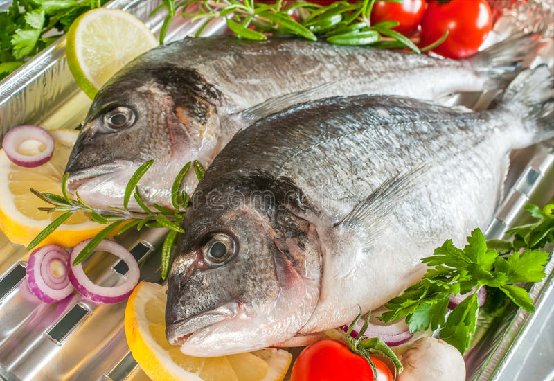 Sea bream fish on a grill. Sea bream fish with the vegetables on a grill stock photo