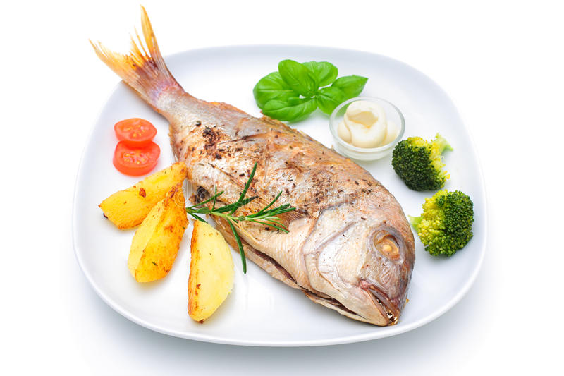 Sea bream fish. With potato on white plate royalty free stock image