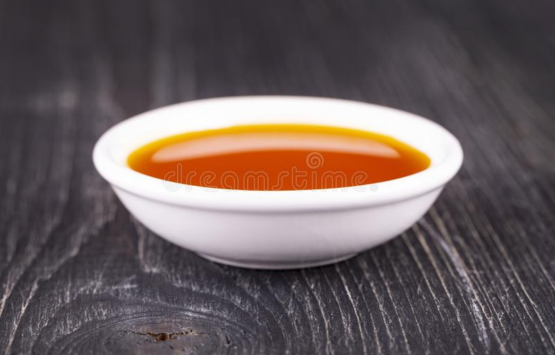 The sea buckthorn oil in the white small Cup on old wooden background. Sea buckthorn oil in the white small Cup on old wooden background stock photography