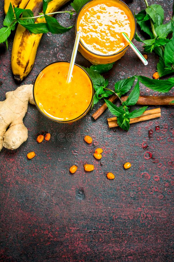 Sea-buckthorn smoothie with banana and mint. On rustic background royalty free stock photo