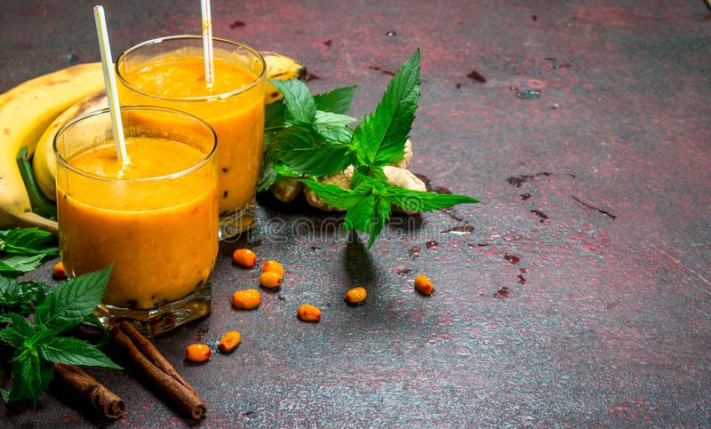 Sea-buckthorn smoothie with banana and mint. On rustic background royalty free stock images