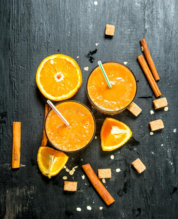 Sea-buckthorn smoothie with lemon and cinnamon. On black background royalty free stock photo